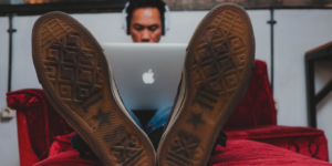 man with laptop and earphones, sitting on sofa with view from soles of his shoes