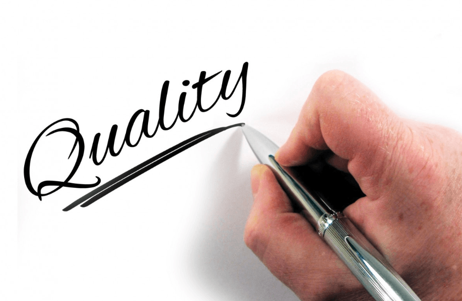 male hand writing word Quality with a pen
